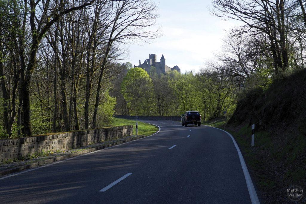 Burg Bourscheid von Straße unterhalb mit Waldkurve und Auto
