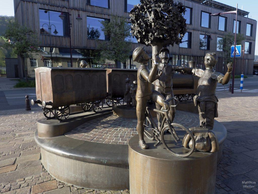 Bronzeskulpturen mit Szene aus Bahn, drei Personen und Velo, Diekirch