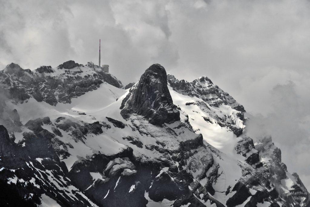 Nahaufnahme Säntis-Spitze mit Sendeturm, schneebedeckt, rausstehende Felsen, wolkig