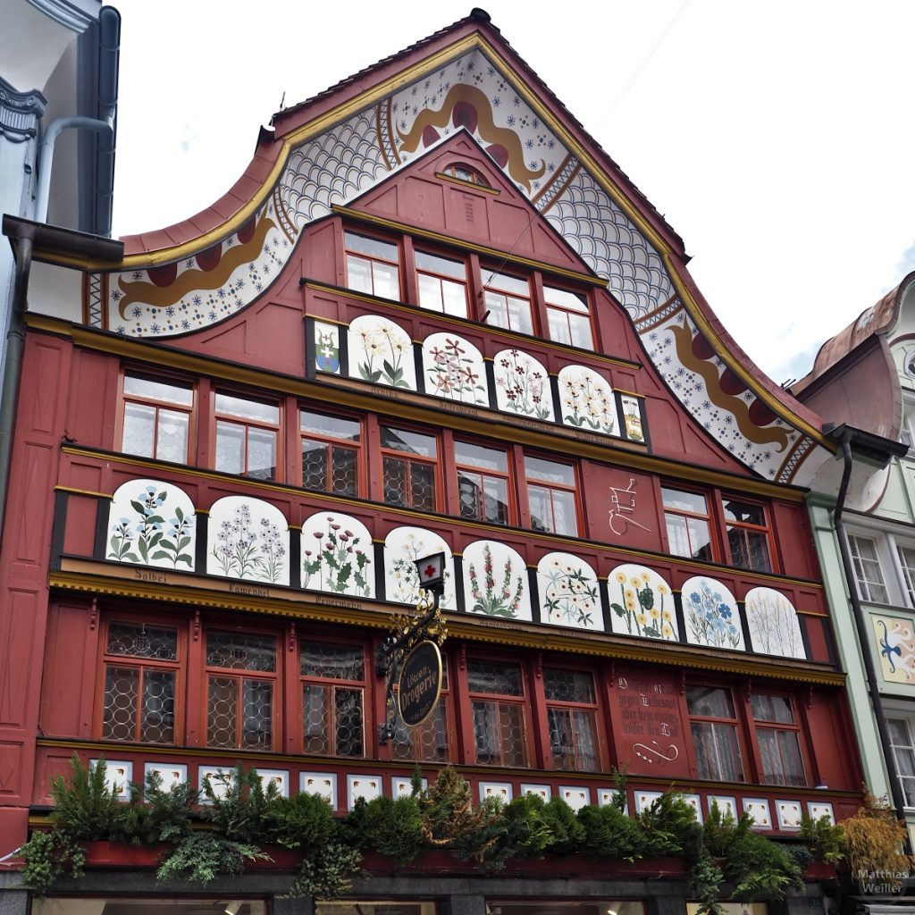 Kräuterbilder auf der bunten Fassade der Apotheke in Appenzell