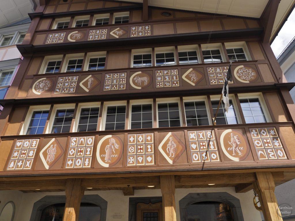 Berufs- und Tiermotive nebst Symbolen auf braunem Grund, Fassade Haus in Appenzell