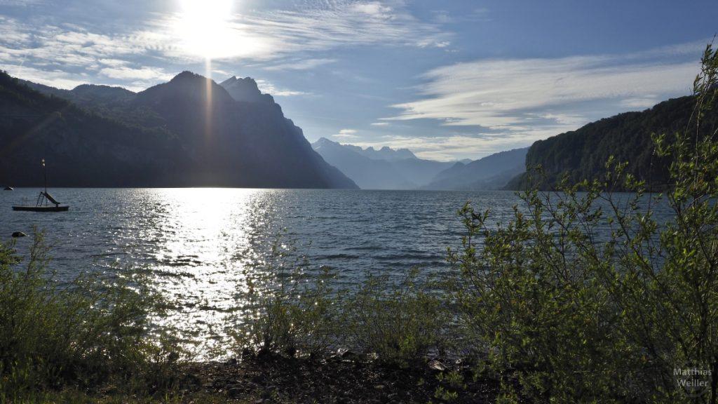 Walensee am Ufer mit Bergkulisse im Sonne im Gegenlicht