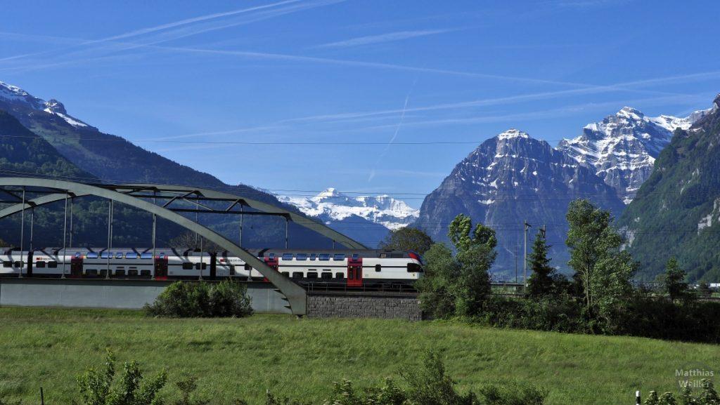 Panorama schneebedeckte Glarner Alpen mit Eisenbahnbrücke und Doppelstockzug