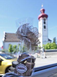 Pralinen mit rotzwiebeliger Kirche Gommiswald im Hintergrund