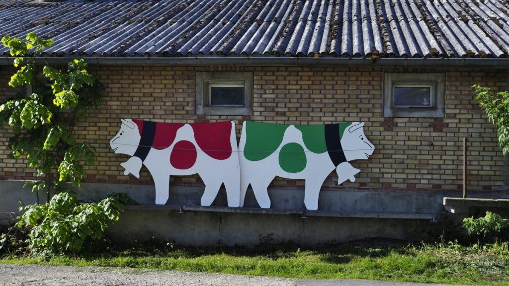 Rote und grüne Kuh als Symbol-Bilder vor Molkerei