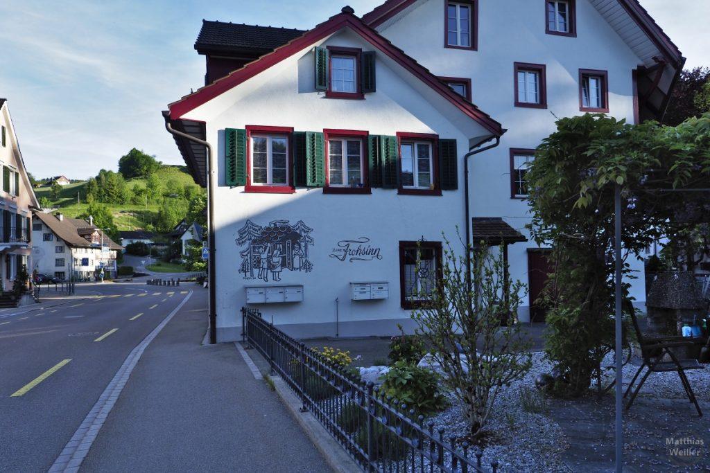 """Gasthof """"Zum Frohsinn"""" in Bauma mit grün-roten Fensterumrandungen auf Weiß"""