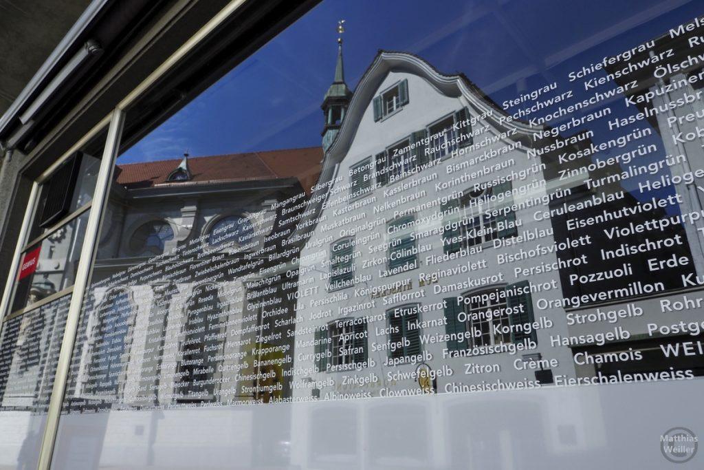 Farbbezeichnungen auf Fenster eines Mediengestalters mit gespilter Fassade und Kirche