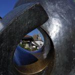Lochblick durch Skulptur auf hsitorische Gebäude in Greifensee und Radler