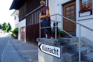 """Holshcnitzfigur und Hund über Richtungsschild """"Küsnacht"""" in Forch"""