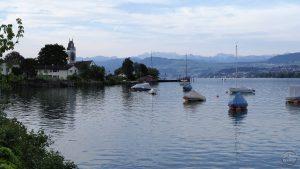 Blick über Seeufer auf Meilen mit Kirche, einzelnen Booten an Bojen, Bergkulisse im Hintergrund