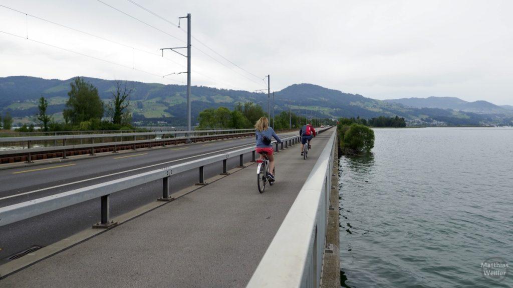 Seedamm Zürichsee mit Radlerin und Radler auf Radweg