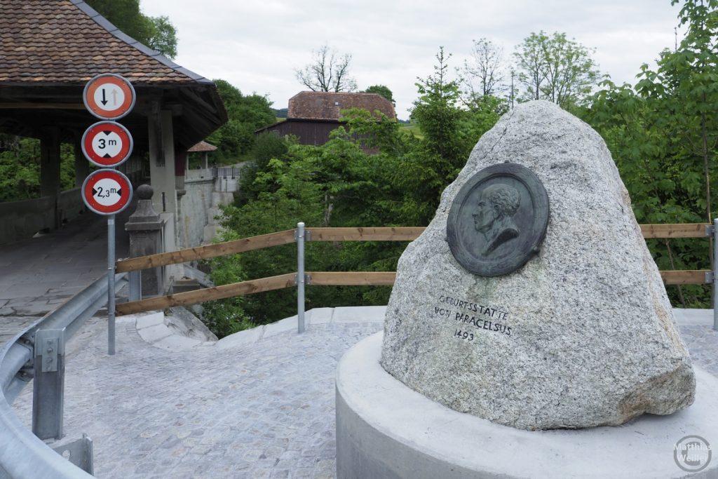 Paracelsus-Denkmalstein an seiner Geburtstätte, im Hintergrund die Teufelsbrücke