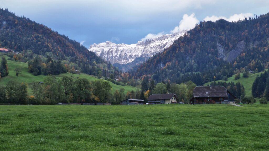 Schrattenfluh mit Schnee im keilförmigen Sichtfenster von grüne Bergwiesen udn herbstlichen Waldhängen mit Bauernhäusern, Entlebuch