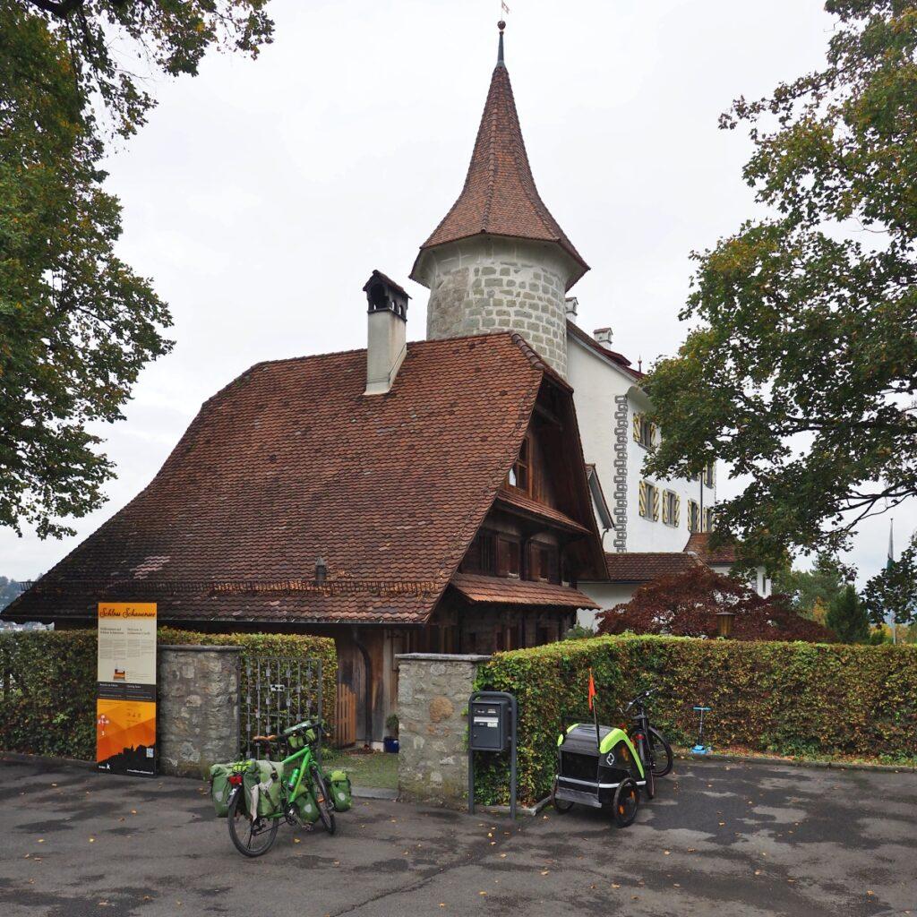 Burg Schauensee mit langem Zigeldachhause, Rundturm, Schlossgebäude weiß, Reisevelo, Velo mit Kinderhänger
