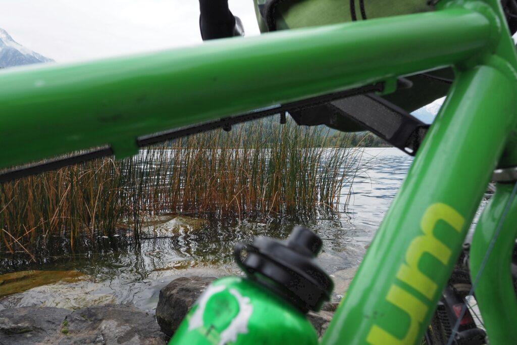 Grüner Velo-Rahmenwinkel und Wasserflache als Guckfenster auf Schilf und See