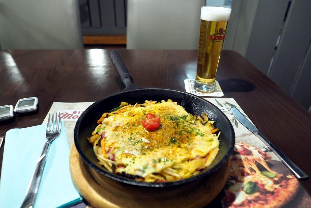Rösti mit Käse überabcken in Eisenpfanne, Bier