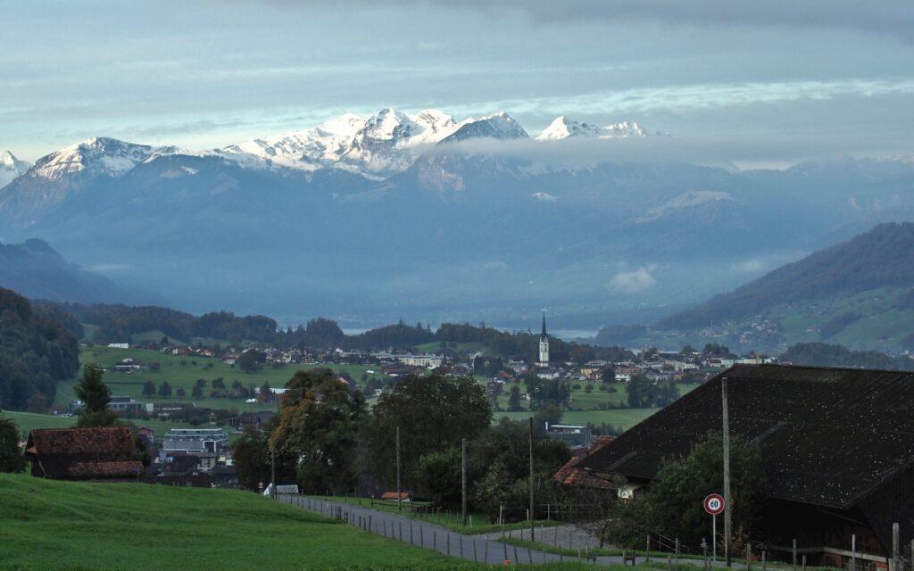 Gipfelkette mit Wolkenshcleier über Sarner See und Kerns mit spitzem Kirchturm