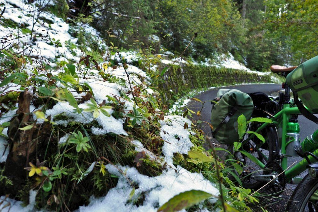 Nahaufnahme bemooste Straßenmauerkurve mit Schneeresten und Ausschnitt grünes Reisevelo