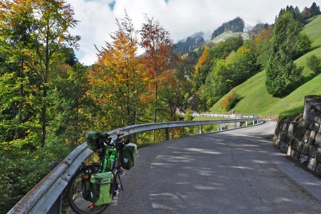 Straßenkurve mit Leitplanke, Herbstbäume, grüne Bergwiese, Schneegriesel und Wolken darüber, aber sonnig, Reisevelo im Vordergrund