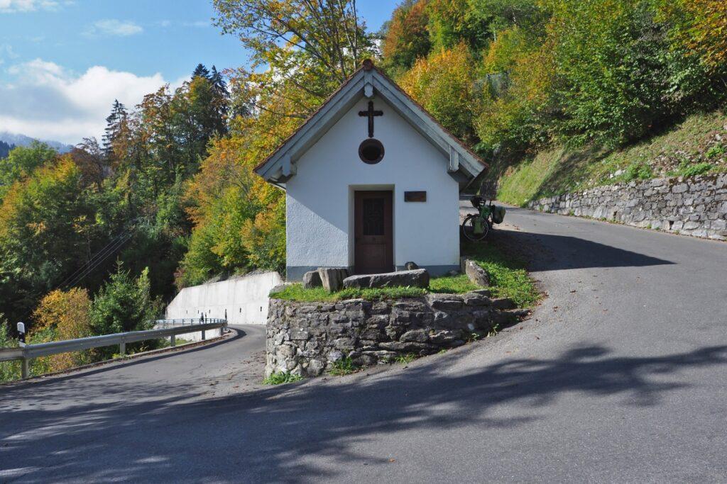 Kapelle in Spitzkehre, Reisevelo, Herbstbäume