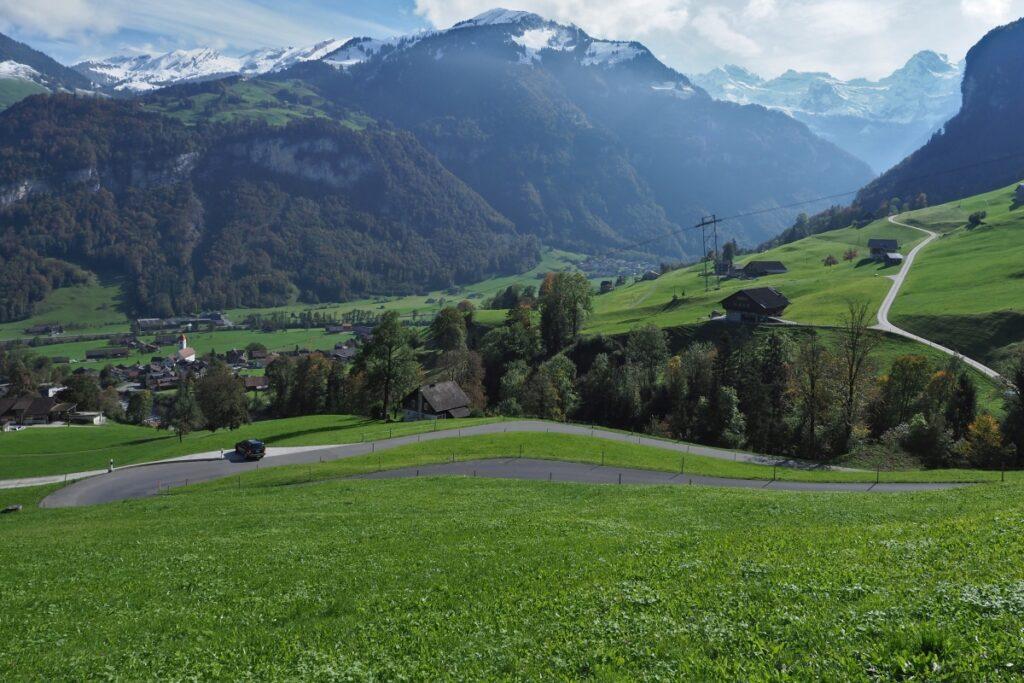 Straßenkurven mit grüner Bergwiesen und Gipfelketten im Hintergrund