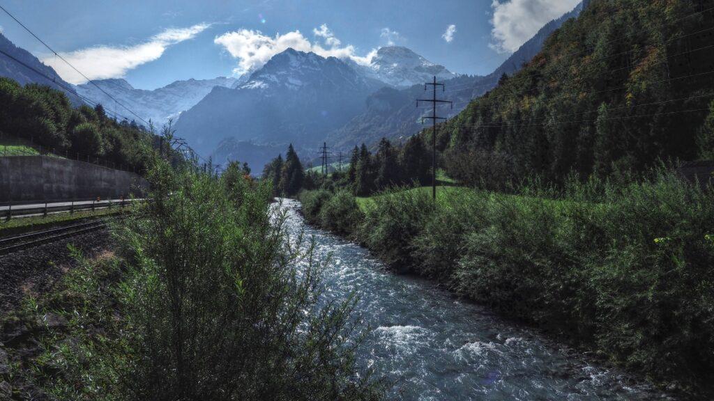 Bergbach, Bahnlinie und Bergstockkulisse im Hintergrund