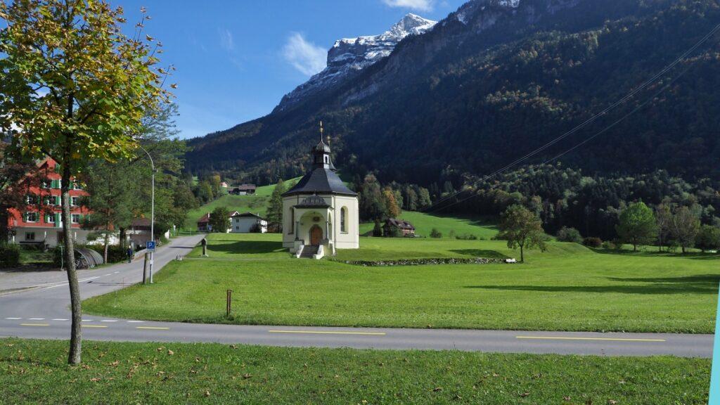 Kapelle Grafenort mit grüner Wiese und Bergstock dahinter
