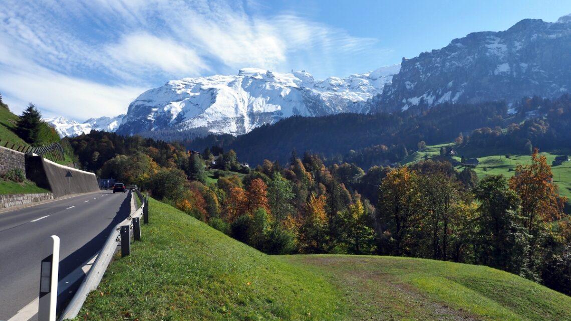 Beschneiter Bergstock mit Herbstatmosphäre un Straße im Vordergrund, Engelberg-Anfahrt