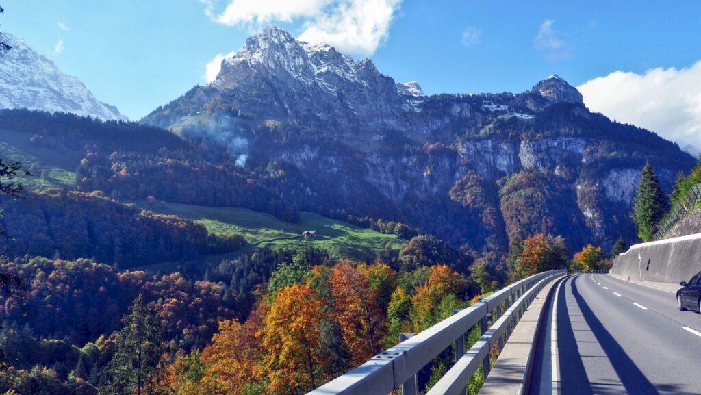 Bergstock mit Herbstfärbung, Straße mit LEitplanke im Vordergrund