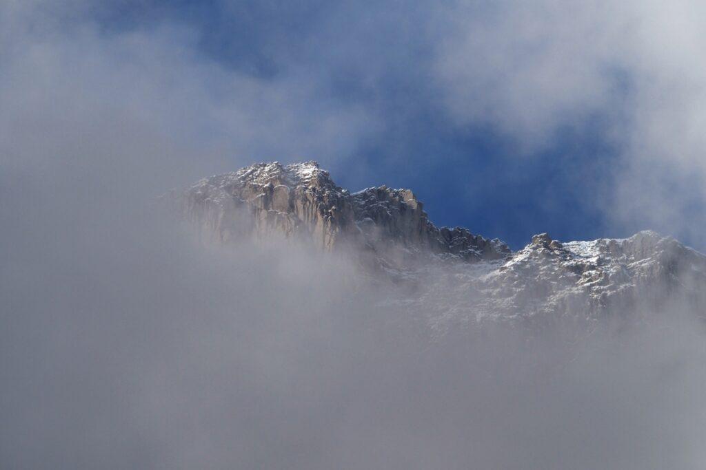 Auftauchneder Berg aus Wolk, Fels und Schnee