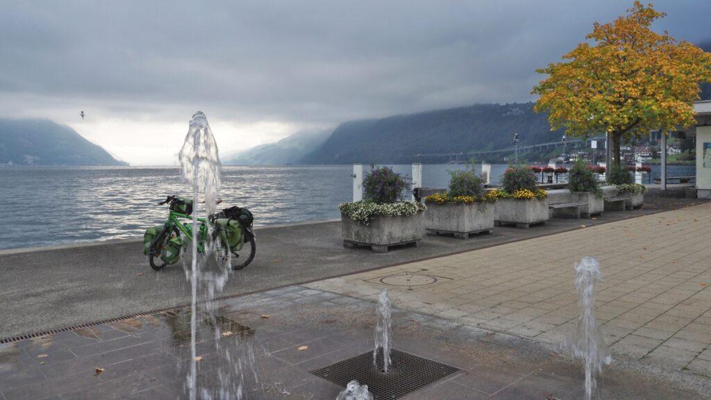 Grünes Reisevelo hinter Bodensprudler und vor See mit Herbstbaum, leicht düstere Stimmung