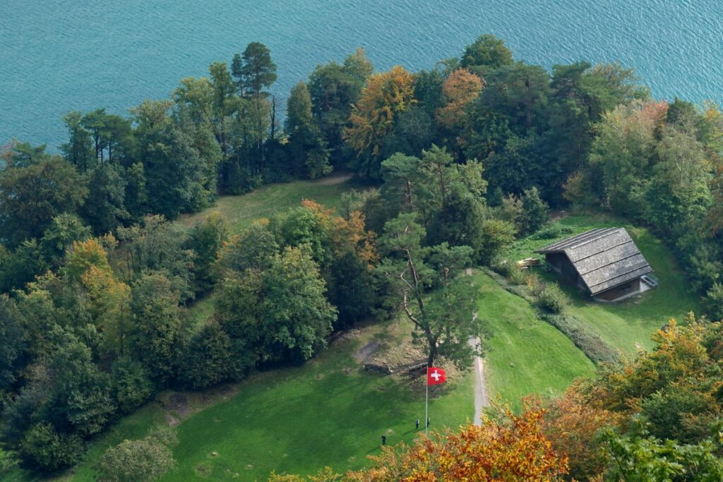 Blick auf Rütliwiese mit Hütte und Schweizer Flagg von oben