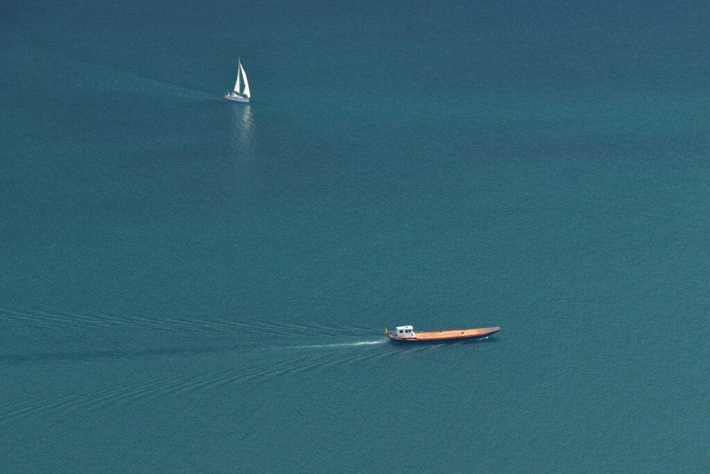 Schiffskahn und Segelboot auf Seefläche von oben