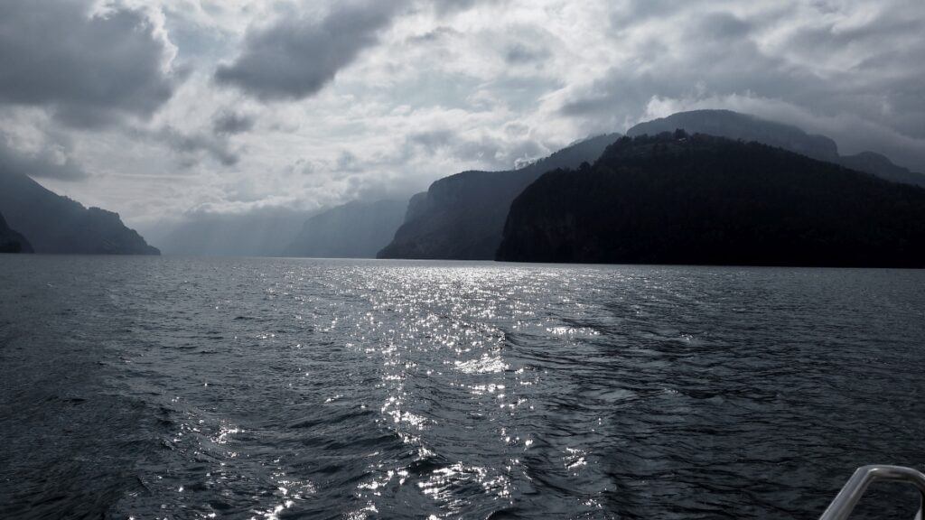 Spiegelnde Wasserfläche des Vierwaldstätter See mit Berghintergrund, dunkel-silbrig
