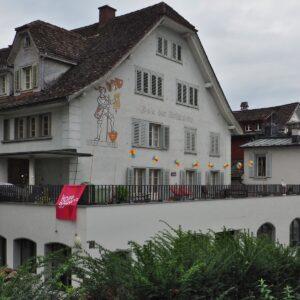"""Haus """"Bote der Urschweiz"""" mit Transparent """"Hopp Schwyz"""""""