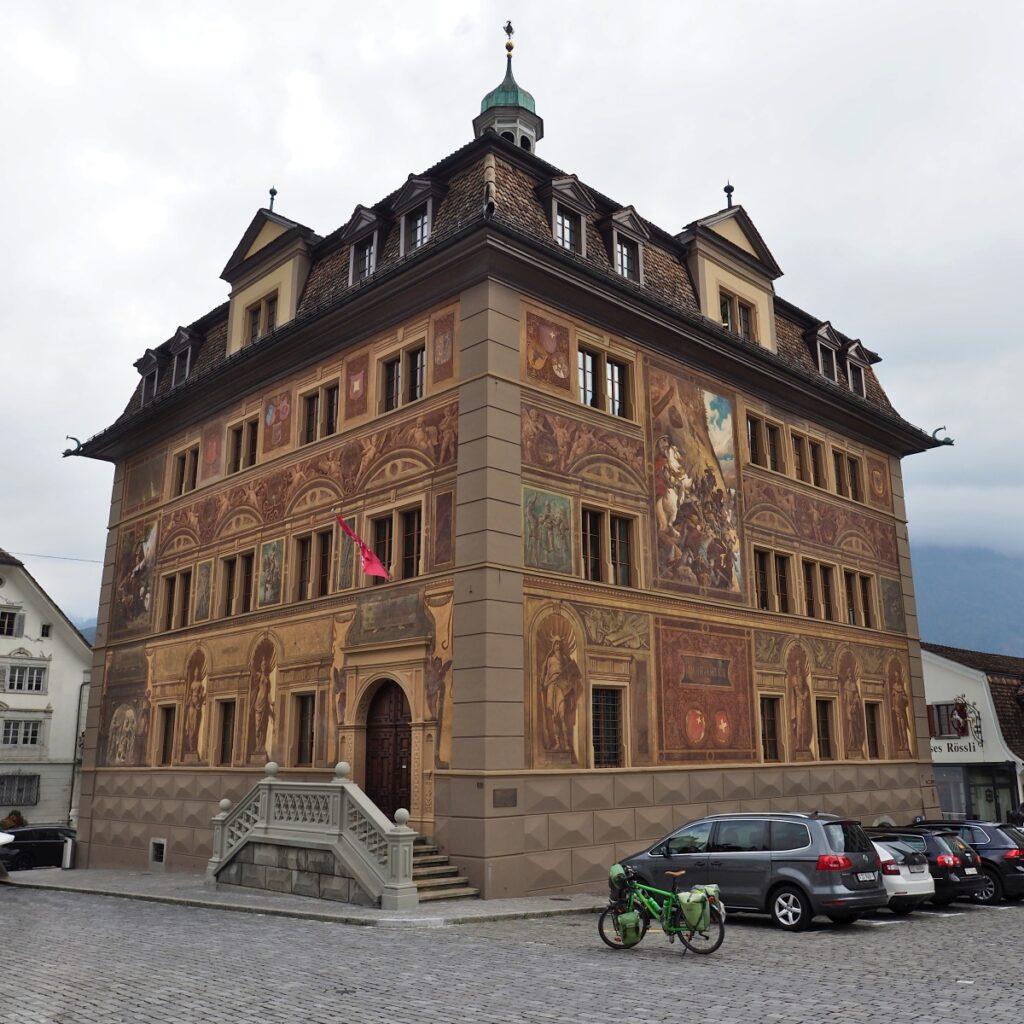 Rathaus Schwyz in perspektivischer Totalen, bemalte Fassade, Reisevelo und Autos