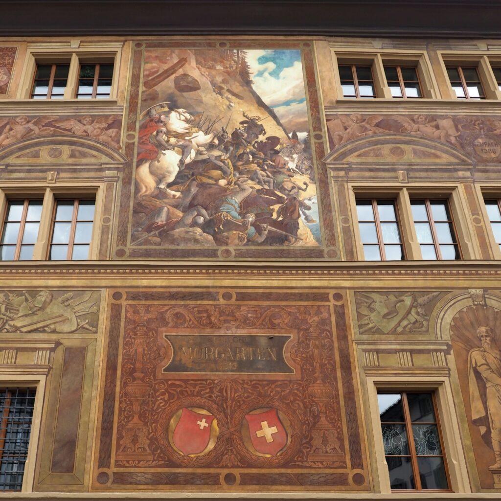 Rathaus Schwyz, Ausschint Fassade mit Morgartenshclacht und Wappen, rote Samttöne