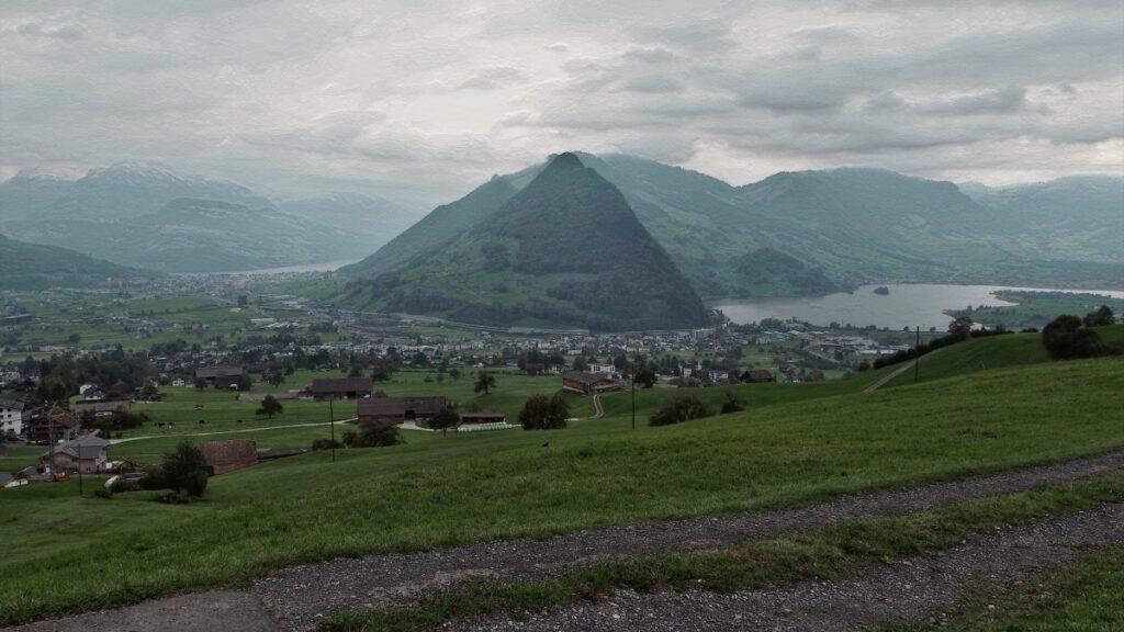 Kegelförmiger Berg bei Goldau mit Seeflächen zu beiden Seiten und Siedlungsebene