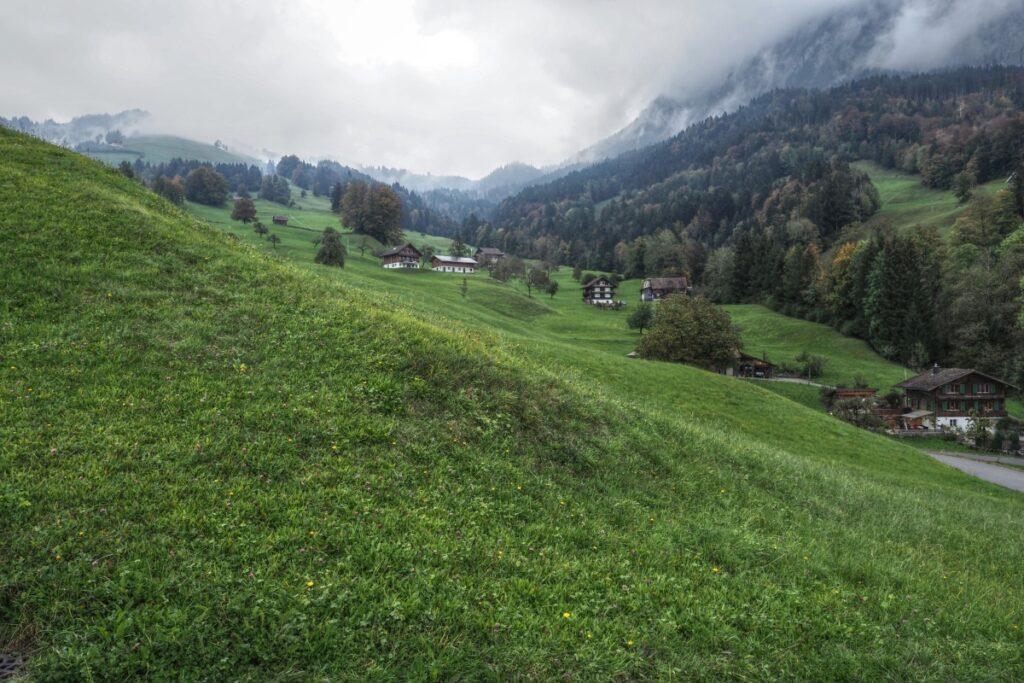 Mostelberg-Auffahrt mit Bauernhäusern auf grünen Weidewiesen und dichtenWolken nach oben hin