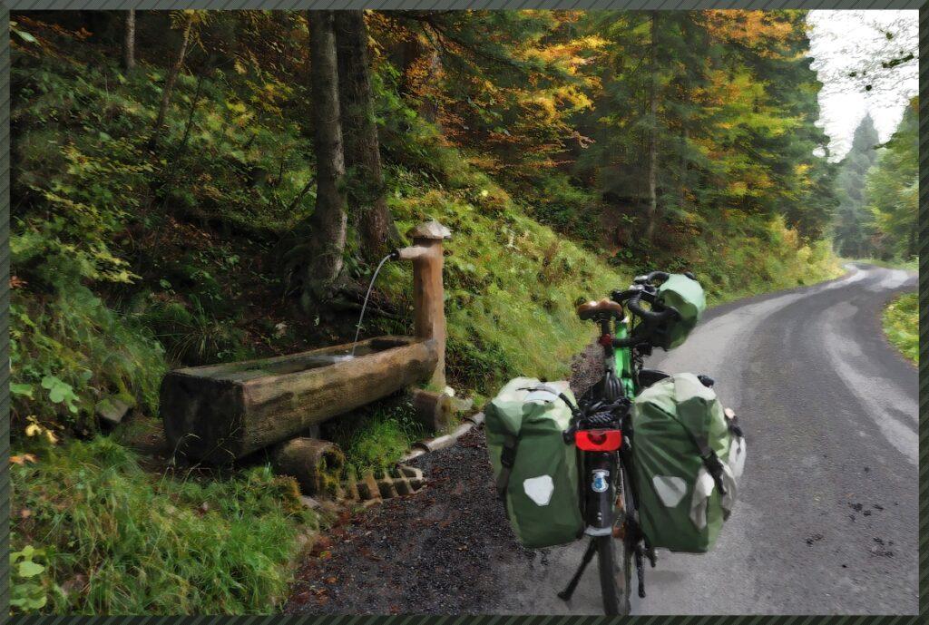 vermaltes Foto mit Brunnen und grünem Reisevelo