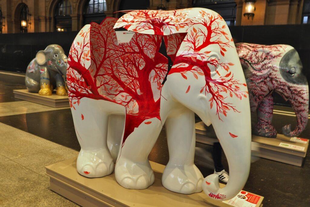 Weiße Elefantskulptur aufgebrichen mit blutrotem Baum als Innenleben
