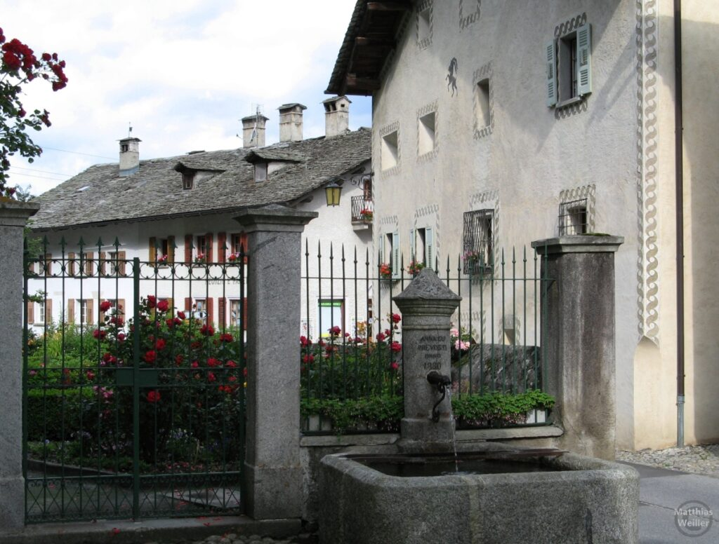 Engadinerhaus, Doppelwelle, Steinbock, weiß/grau, Brunne im Vordergrund, Vicosoprano