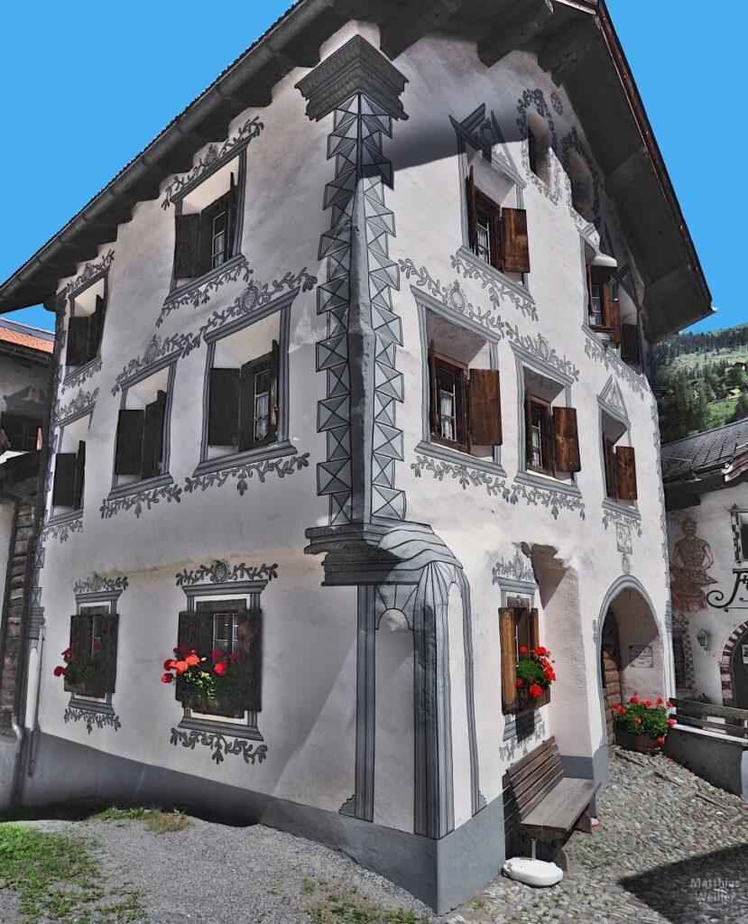 Engadinerhaus, starke Ornamente, weiß/grau, rote Geranien, Bergün