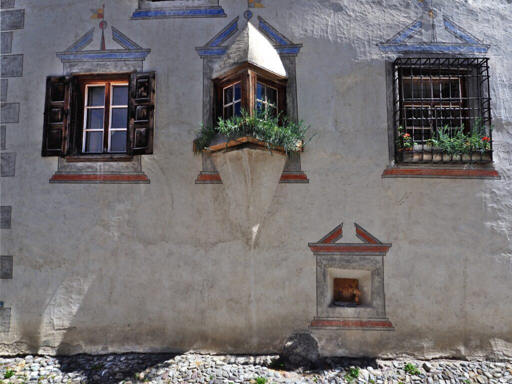 Engadinerhaus, Spitzerker mit grünen Pflanzen, Bergün