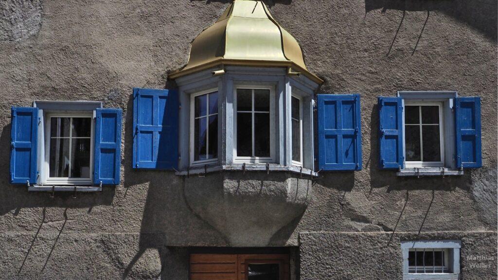 Engadinerhaus, Erker mit goldenem Dach, blaue Läden, Bergün