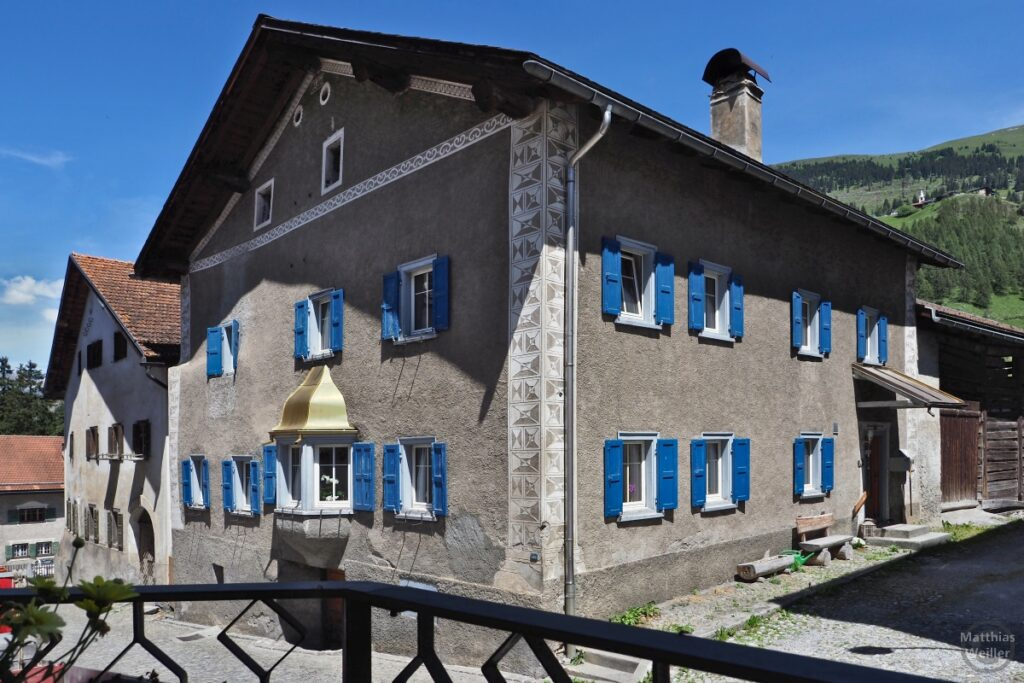 Engadinerhaus, grau/blau, Erker mit goldenem Dach, Bergün