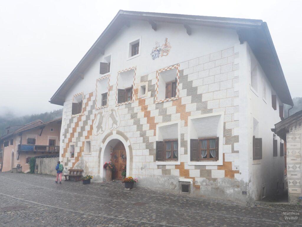 Engadinerhaus, treppiges Muster weiß/grau/ocker, Doppelsteinbock, Scuol