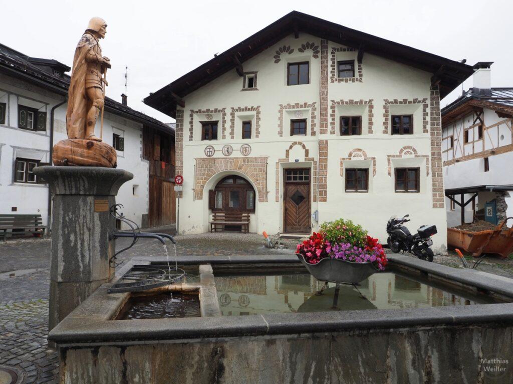 Engadinerhaus mit Mauermustern, hinter Brunnen, Scuol