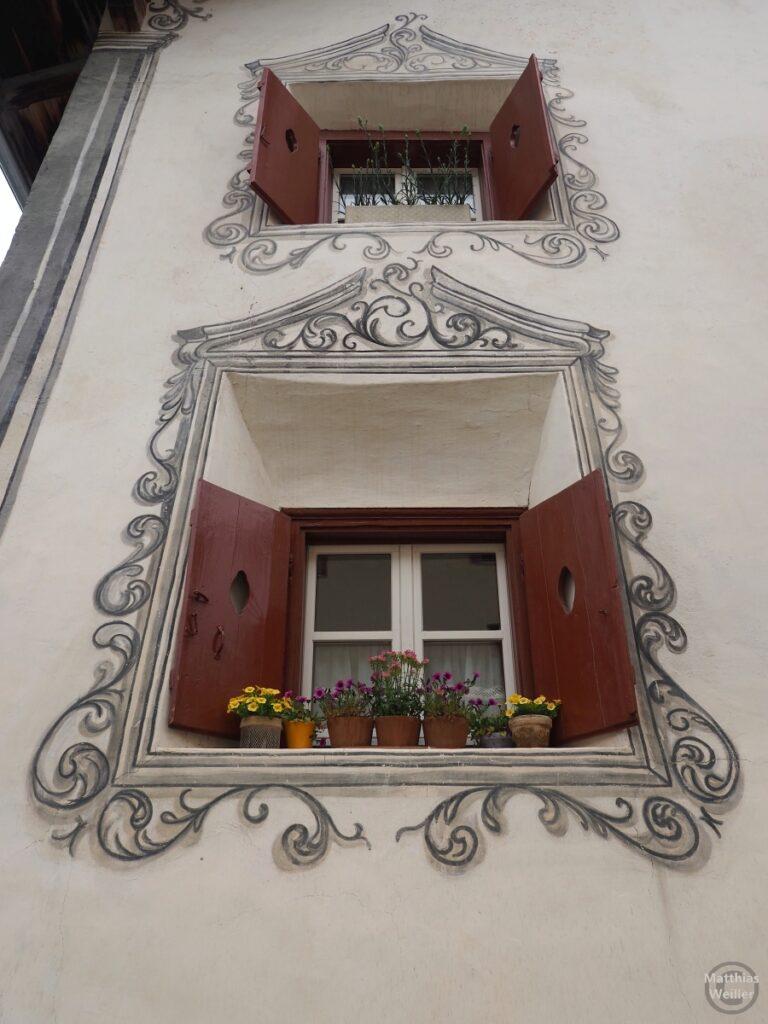 Engadinerhaus, 2 Fenster übereinander weiß/grau/graun, geschwungene Ornamente, Scuol