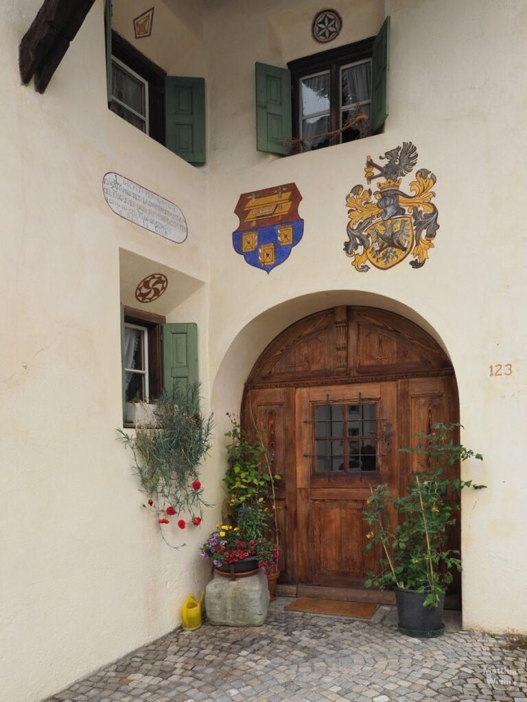 Engadinerhaus, Eingang, Wappen, Fenster, Blumen, Scuol